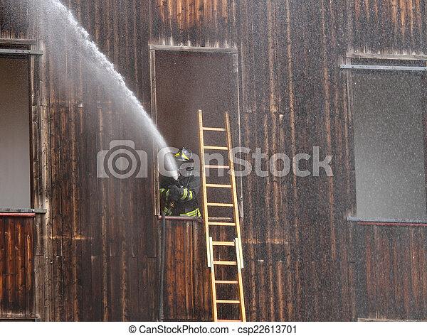Bombero apaga un fuego con una manguera - csp22613701