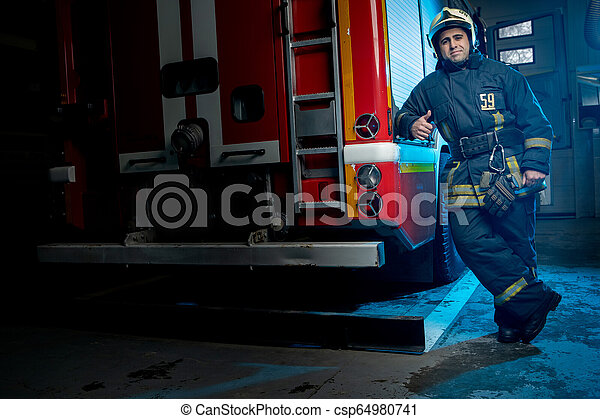 Una foto larga de un bombero en el camión de bomberos - csp64980741