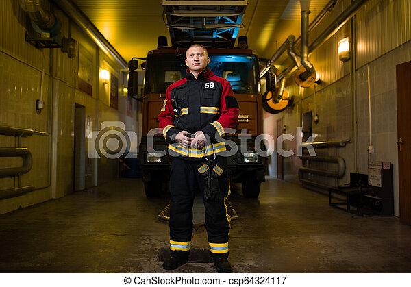 Foto de larga duración de bombero en el fondo del camión de bomberos - csp64324117