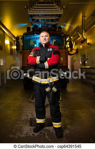 Una foto de larga duración de un joven bombero en el fondo del camión de bomberos en la estación - csp64391545