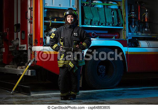 Una foto larga de mujer cerca del camión de bomberos - csp64883805