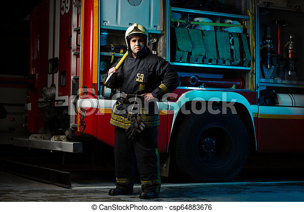 Imágenes de larga duración de un bombero con piquete cerca del camión de bomberos en la estación - csp64883676