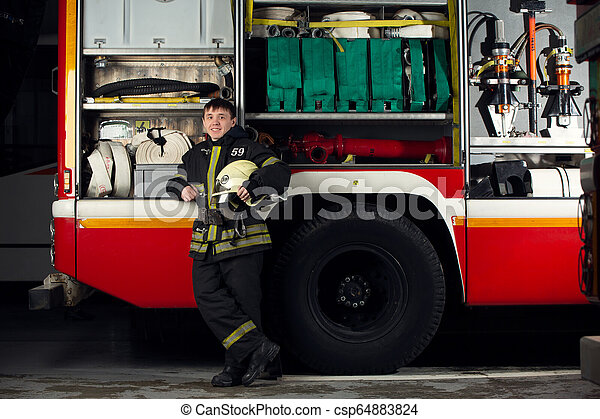 Imágenes de bombero cerca del camión de bomberos - csp64883824