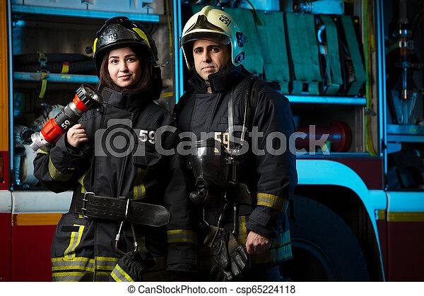Imágenes de bombero y mujer cerca del camión de bomberos - csp65224118