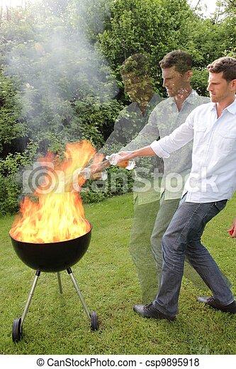 BBQ con fuego a un joven - csp9895918