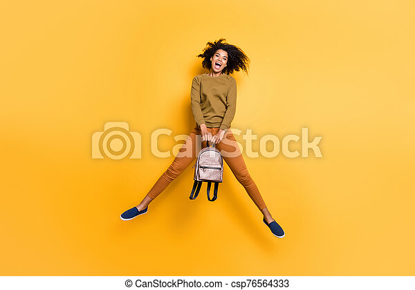 Full length body size photo of cheerful charming positive cute beautiful pretty sweet curly wavy youngster holding handbag with hands jumping with having known about weekend isolated over vivid color background - csp76564333