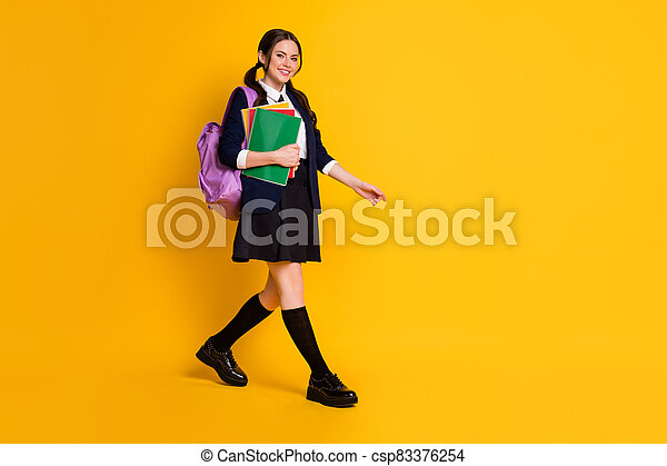 Full length body size view of her she nice attractive pretty cheerful schoolgirl going to secondary school carrying literature isolated on bright vivid shine vibrant yellow color background - csp83376254