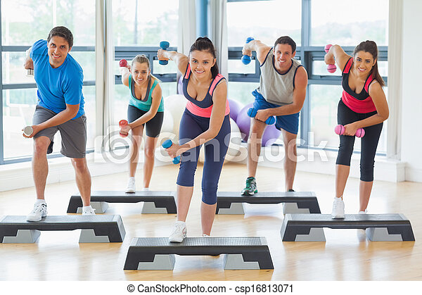Full length of instructor with fitness class performing step aerobics exercise with dumbbells in a gym - csp16813071