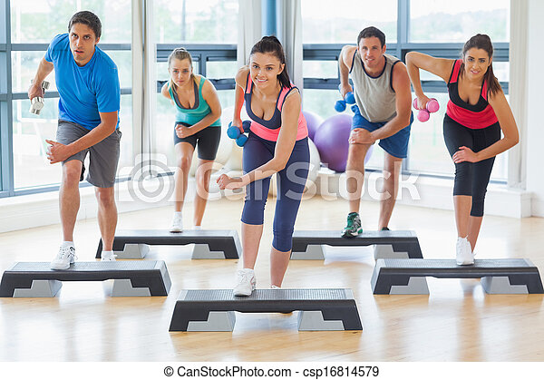 Full length of instructor with fitness class performing step aerobics exercise with dumbbells in a gym - csp16814579