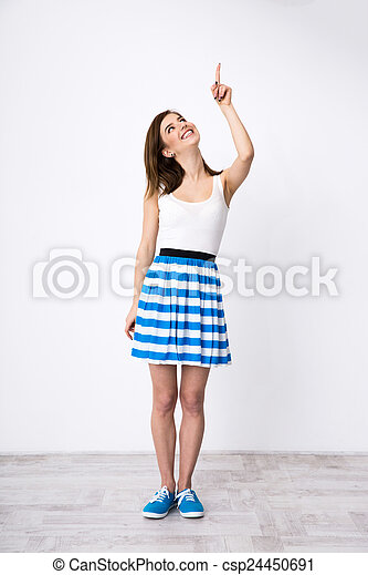 Full length portrait of a happy woman pointing up - csp24450691