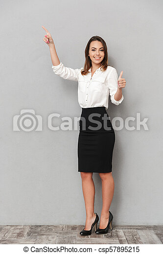 Full length portrait of a smiling young business woman - csp57895215