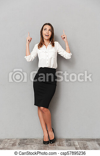 Full length portrait of a smiling young business woman - csp57895236