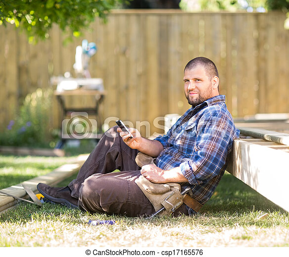 Full length portrait of confident carpenter text messaging on cellphone while leaning on wooden frame at construction site - csp17165576