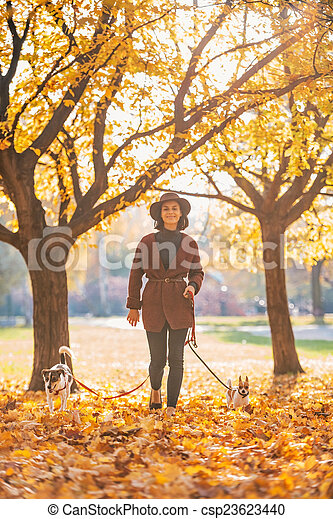 Full length portrait of happy young woman walking with dogs outd - csp23623440