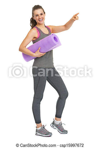 Full length portrait of smiling fitness young woman with fitness mat pointing on copy space - csp15997672