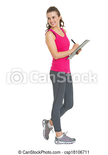 Full length portrait of smiling fitness young woman writing in clipboard and looking on copy space - csp18106711