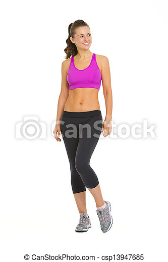Full length portrait of smiling fitness young woman looking on copy space - csp13947685
