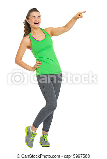 Full length portrait of smiling fitness young woman pointing on copy space - csp15997588