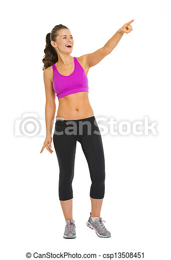 Full length portrait of smiling fitness young woman pointing on copy space - csp13508451