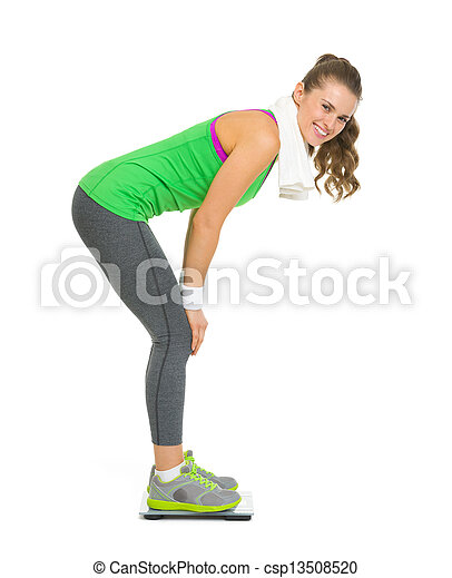 Full length portrait of smiling fitness young woman weighing on scales - csp13508520