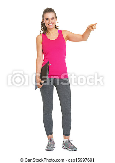 Full length portrait of smiling fitness trainer with clipboard pointing on copy space - csp15997691