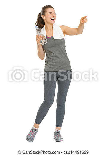 Full length portrait of smiling fitness young woman with bottle of water pointing on copy space - csp14491639