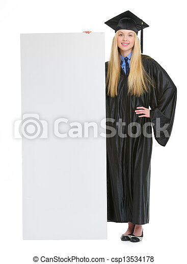 Full length portrait of smiling young woman in graduation gown showing blank billboard - csp13534178