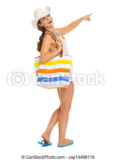 Full length portrait of smiling young woman with beach bag pointing on copy space - csp14499116