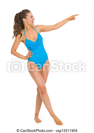 Full length portrait of smiling young woman in swimsuit pointing on copy space - csp13311904