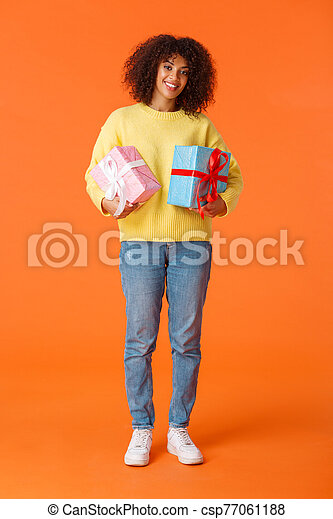 Full-length vertical shot attractive cheerful african american woman prepared for holidays, bought presents for family, smiling cheerful holding two boxed gifts, standing orange background - csp77061188