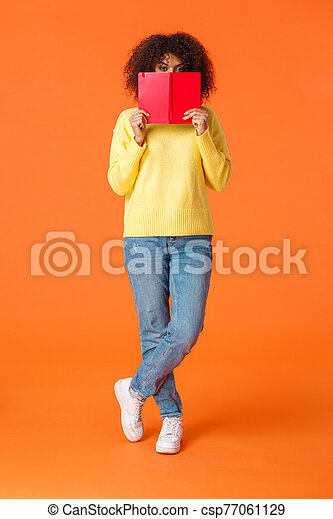 Full-length vertical shot shy and cute african-american modern urban girl with afro haircut, hiding face behind red notebook and peeking camera, writing in diary, standing orange background - csp77061129
