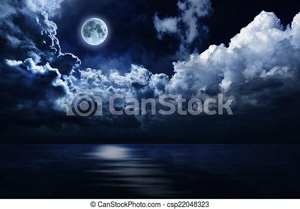 Full moon in night sky over water - csp22048323