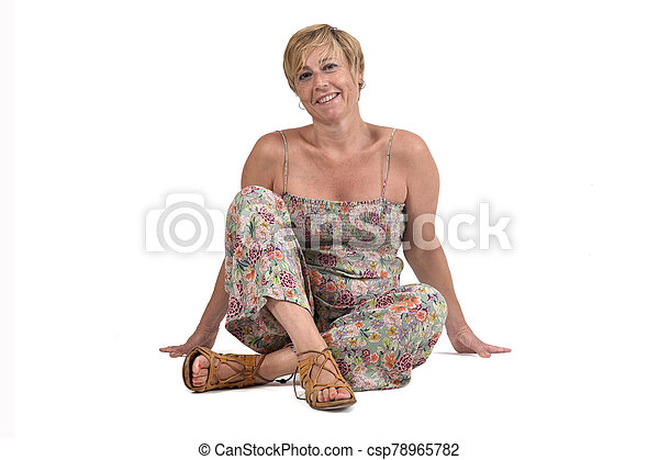 full portrait of middle aged woman sitting on the ground on white - csp78965782
