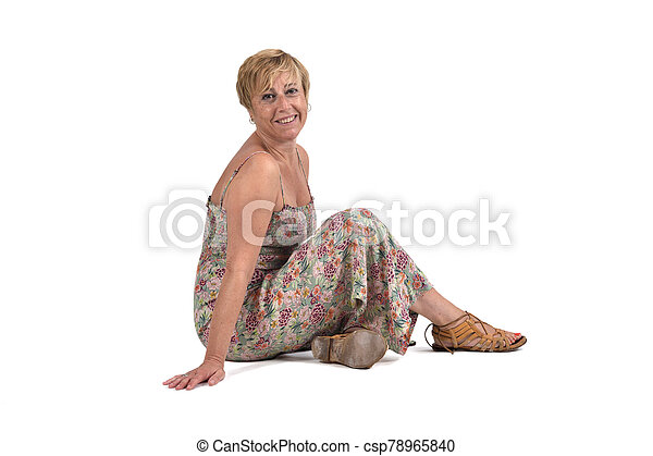full portrait of middle aged woman sitting on the ground on white - csp78965840