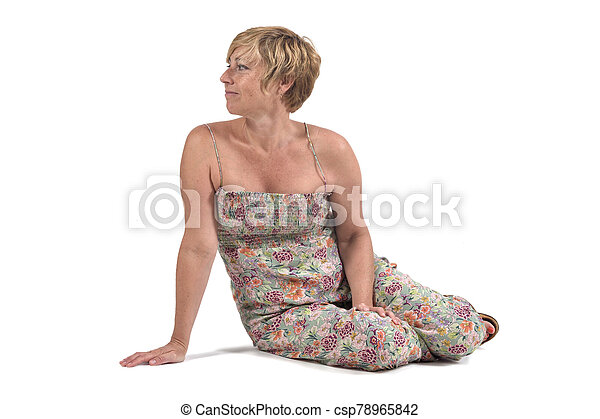 full portrait of middle aged woman sitting on the ground on white - csp78965842