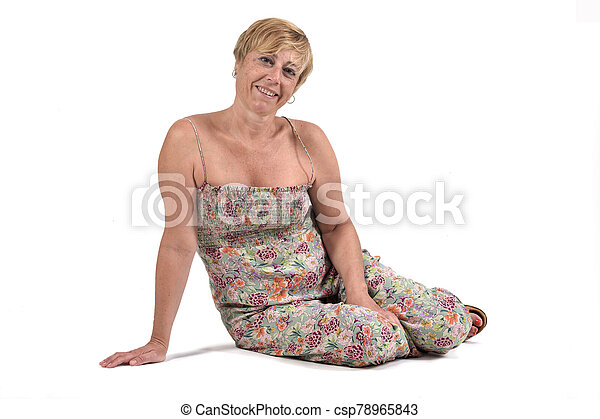 full portrait of middle aged woman sitting on the ground on white - csp78965843