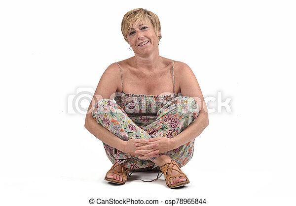 full portrait of middle aged woman sitting on the ground on white - csp78965844