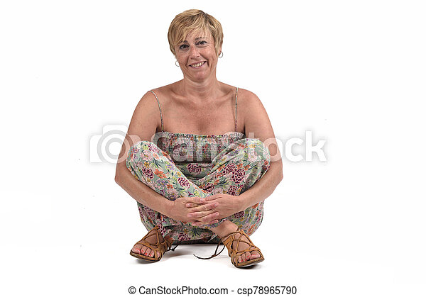 full portrait of middle aged woman sitting on the ground on white - csp78965790