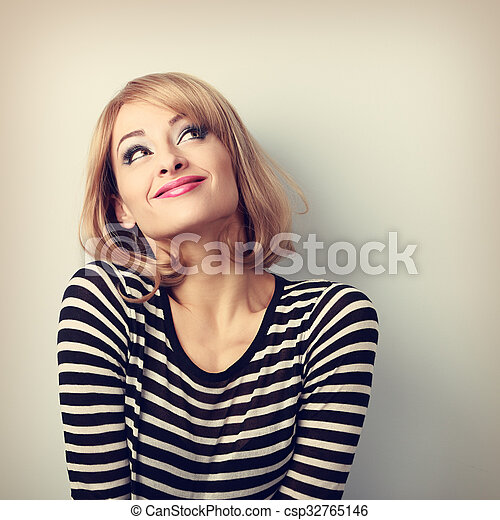 Fun beautiful thinking blond young woman in sweater looking up  - csp32765146