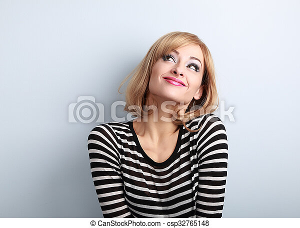 Fun beautiful thinking blond young woman in sweater looking up on blue background - csp32765148