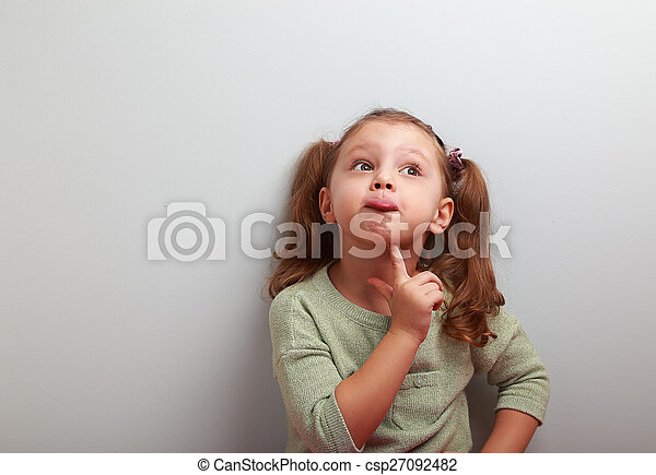 Fun grimacing girl thinking and looking up on blue background - csp27092482