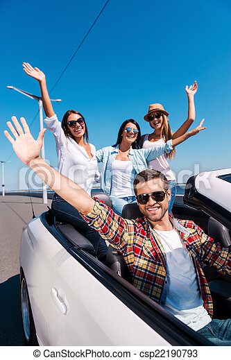 Fun travel. Group of young happy people enjoying road trip in their white convertible and raising their arms up - csp22190793