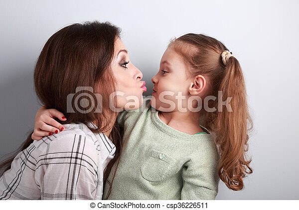 Funny amusing young mother wanting to kiss her comical grimacing daughter in studio - csp36226511