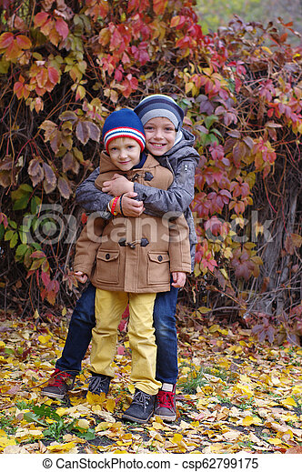 Funny and happy children are played against the background of autumn yellow leaves - csp62799175