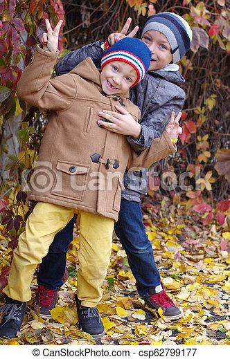 Funny and happy children are played against the background of autumn yellow leaves - csp62799177