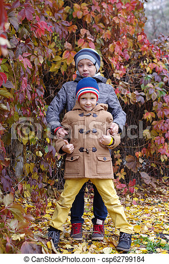 Funny and happy children are played against the background of autumn yellow leaves - csp62799184