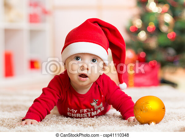Funny baby lying on tummy wearing Santa hat and suit in front of Christmas tree - csp41110348