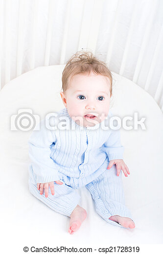 Funny baby sitting in a white round crib - csp21728319