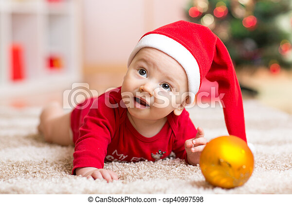 3b69ebb59d6cf Funny baby wearing Santa hat and suit. Kid boy lying on tummy in front of