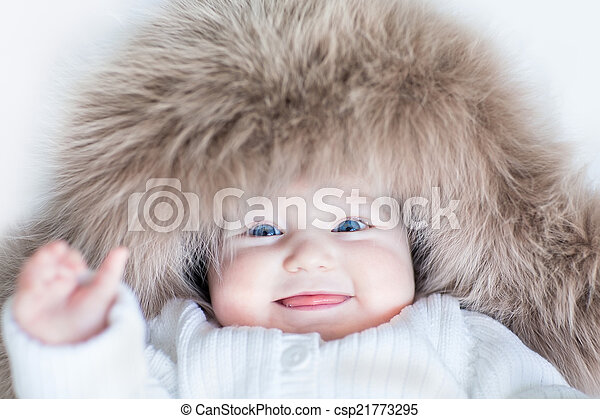 Funny cute baby girl with big blue eyes wearing a huge winter ha - csp21773295